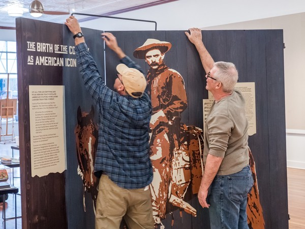 two people hold up and place metal brace across two large wooden panels of cowboy image