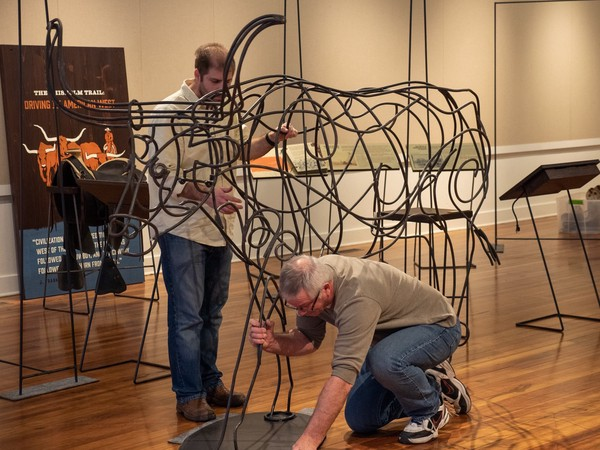 three people move longhorn sculpture into place within a gallery