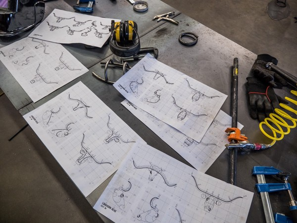 printout plans for the heads of longhorn sculptures amid clamps, gloves, and ear protection