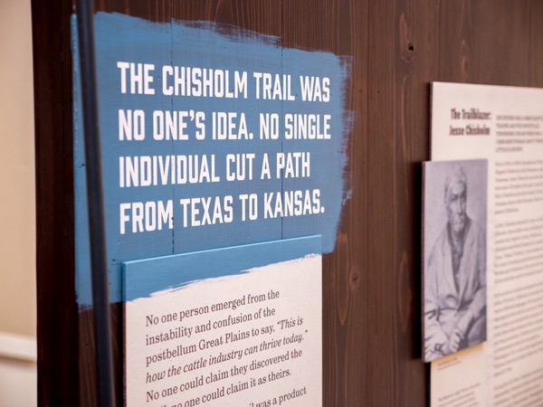 white stenciled text over blue paint with rough brush stroke edges: 'The Chisholm Trail was no one's idea. No single individual cut a path from Texas to Kansas.'
