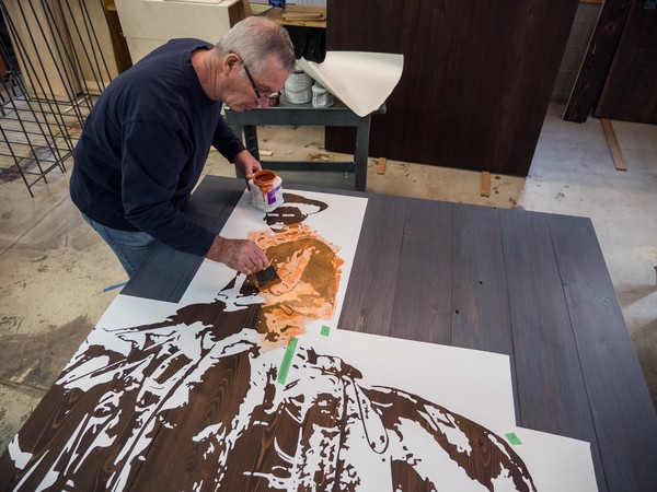 man paints orange stencil layer of cowboy image on dark stained cedar panel