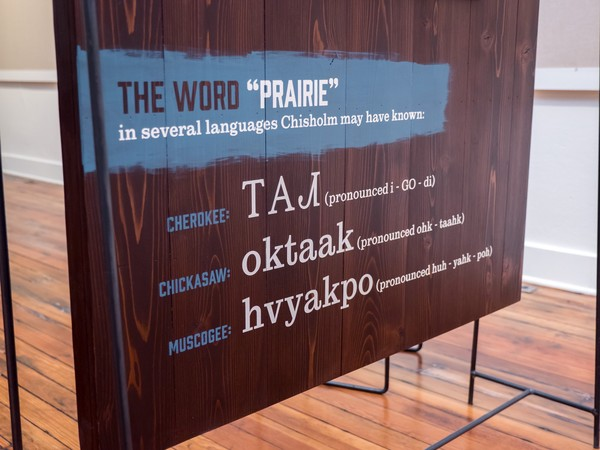 stenciled text of the word prairie in several languages: Cherokee, Chickasaw, and Muscogee
