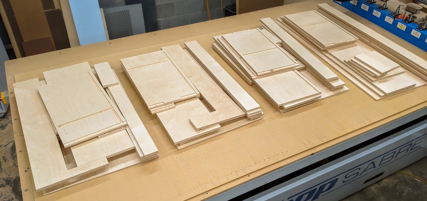 stacks of plywood parts on table of CNC router