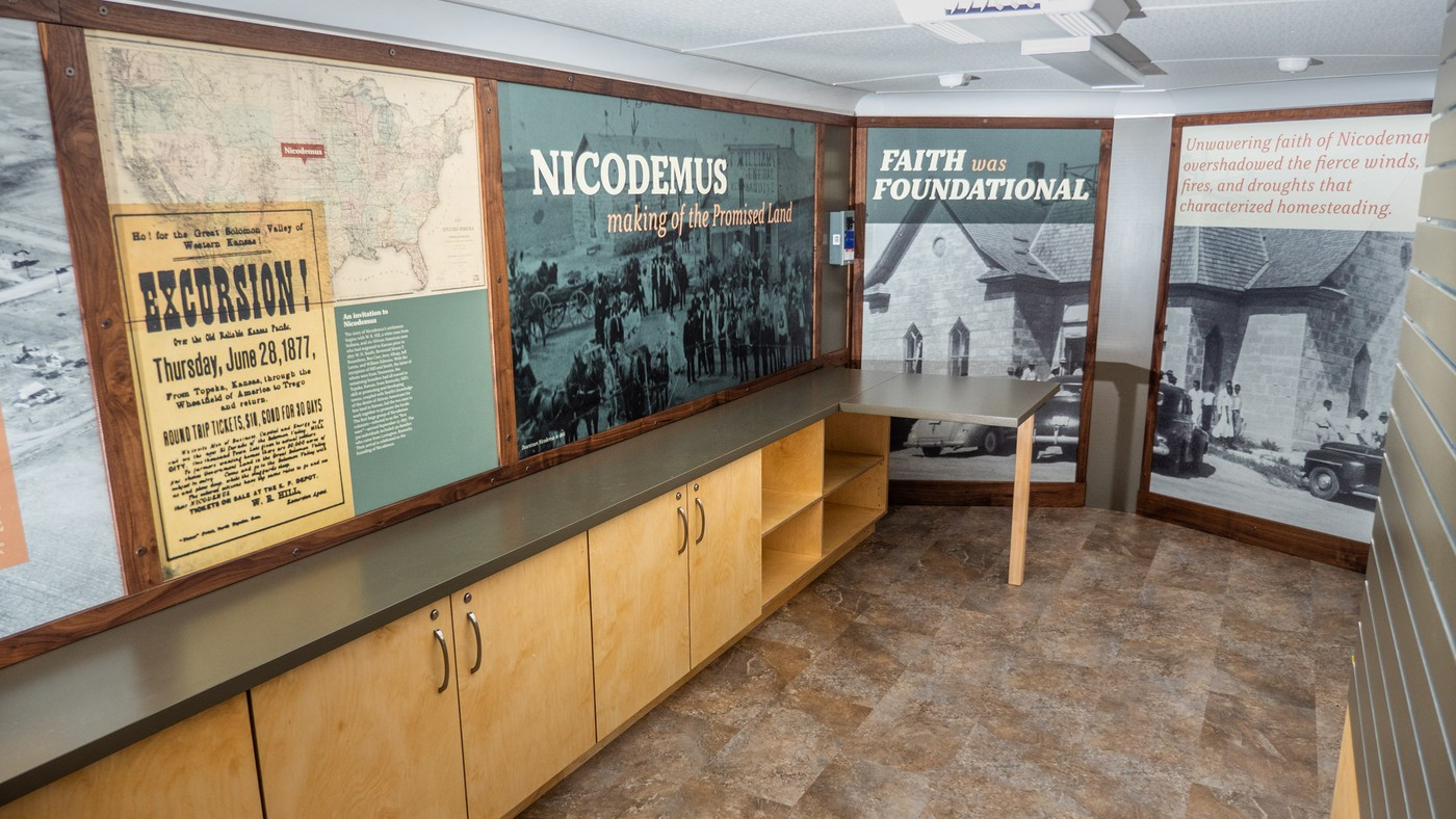 large text and graphic layouts including historic photos in walnut boarders covering walls of nice trailer interior