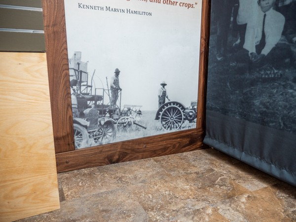 lower portion of interpretive panel showing historic photo of men driving farm equipment